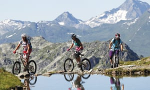 Three mountain bikers on a trail amid the Alps on the Les Arcs bike trail, France.