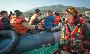 Sarandon greets refugees arriving on a rubber dinghy.