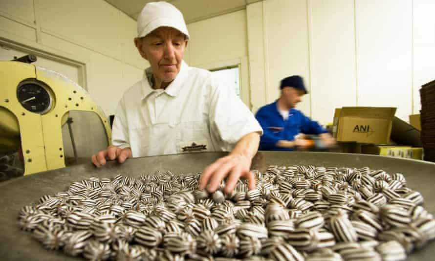 Older worker sorting sweets in factory