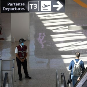 """An airport employee wearing a """"Smart-Helmet"""" portable thermal scanner checks the temperature of passengers and staff at the Fiumicino airport in Rome, Italy, on 11 May 2020."""