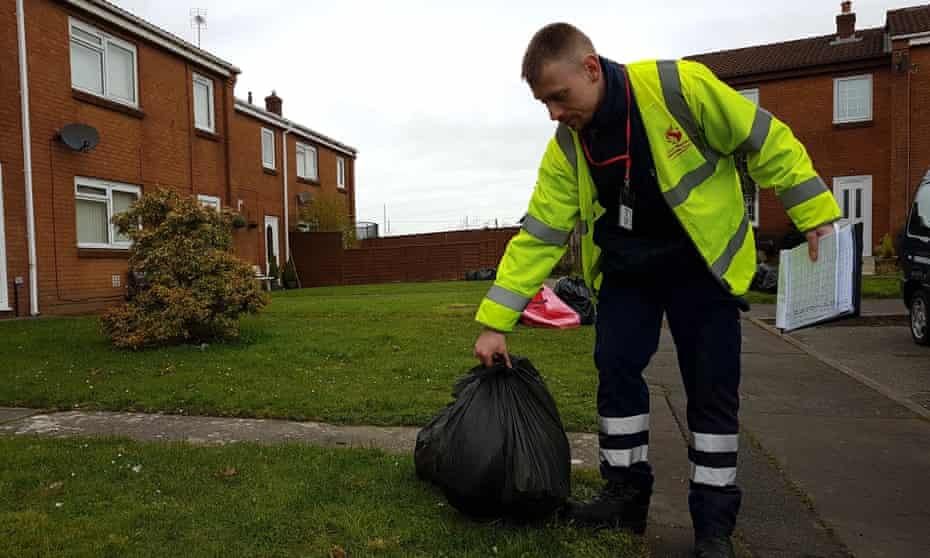Scott Matthews of Swansea council checks bags on a housing estate.