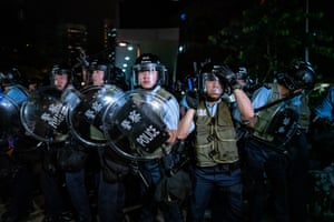 Police officers charge towards protesters in Hong Kong