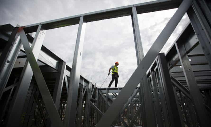 A construction worker wears a tether as he stands on steal beams at the Oval Quarter, a shared ownership, private and social residential housing complex.