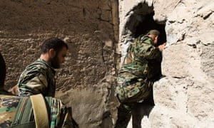 YPG fighters move through a hole opened by the YPG on the side of a building, to avoid being spotted by ISIS snippers as they move towards the front line.