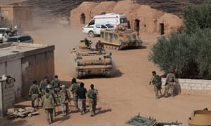 Turkey-backed Syrian rebel fighters drive tanks near the border town of Tal Abyad