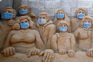 A sand sculpture by the Palestinian artist Rana al-Ramlawi is dressed with masks in Gaza City, Gaza Strip