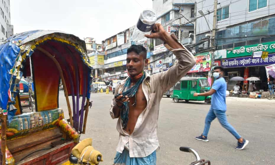 A rickshaw puller pours water on head during hot weather in Dhaka, Bangladesh
