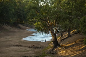 Two men watch fresh water flow along the Darling Barka river in north-west NSW following a years-long drought.