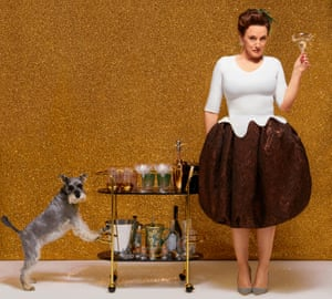 Grace Dent against gold background, with drinks trolley and glass in hand, and dog on other side of trolley
