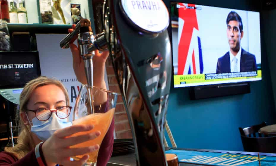 A Manchester pub worker pulls a pint as Rishi Sunak discusses the economy on a news programme