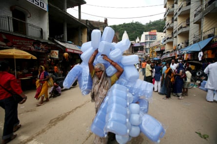 A woman carrying large number of plastic containers in Haridwar, Uttarakhand, India.