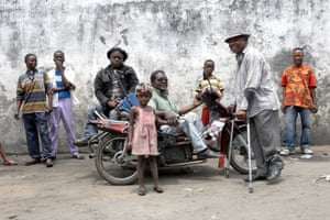 Core members of the Congolese band Staff Benda Bilili in Njilli, Kinshasa, Democratic Republic of the Congo, 2009: Ricki Likabu (trilby), Theo Ntsituvuidi (beret), and Coco Ngambali (on bike). The musicians went from sleeping rough to world fame, winning the 2009 artist award at the World Music Expo. .