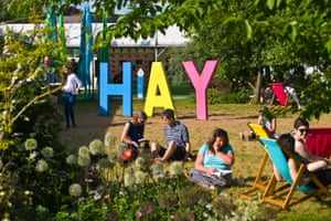 People relaxing on lawn in late afternoon summer sunshine in garden area at Hay Festival 2018 Hay-on-Wye Powys Wales