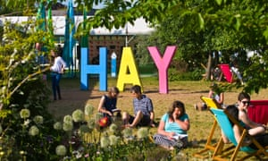 People relaxing on lawn in late afternoon summer sunshine in garden area at Hay Festival