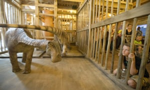 A visitor looks into a cage containing a model dinosaur on the ark.