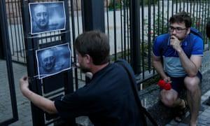 A man hangs a picture of Arkady Babchenko on a fence outside the Russian embassy in Kiev, Ukraine.
