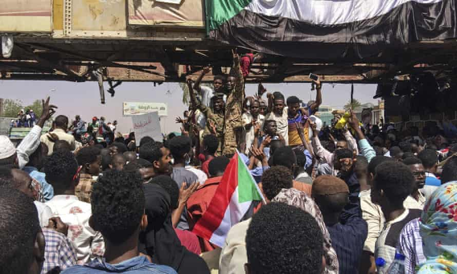 Sudanese soldiers flash the victory sign as they stand among protesters at a demonstration near the military headquarters in Khartoum