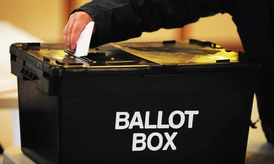 Man placing voting slip in ballot box
