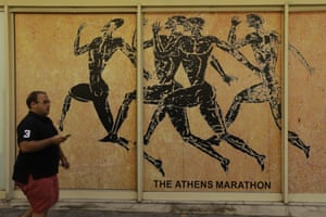 A man passes a store front of souvenir shop in the Plaka tourist district of Athens, Tuesday, July 28, 2015. Emissaries from Greece's international creditors are holding preparatory talks with Greek officials as the aim is to thrash out the terms of the deal before Aug. 20, when Greece must make a debt payment that it cannot afford without new loans. (AP Photo/Thanassis Stavrakis)