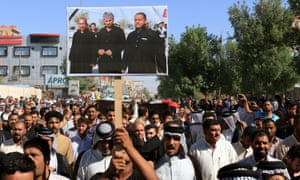 At a funeral procession, Iraqis carry the picture of the hostages who were kidnapped and then executed by Islamic State group.