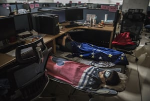 Employees sleep in their cubicle in the research and development area after lunch at the Bantian campus .