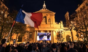 A French flag is waved as people gather on the Place de la Sorbonne in Paris to watch a live broadcast on a giant screen of a national homage at the Sorbonne University to French teacher Samuel Paty.