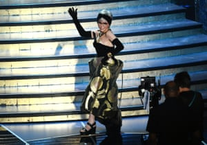 Actor Rita Moreno walks onstage wearing a dress she first wore in 1962 when she won an Oscar