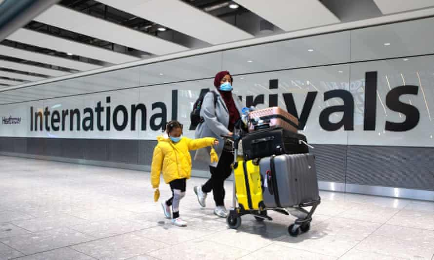 Woman and child pushing trolley at Heathrow Terminal 5.