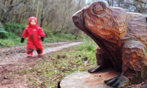 A toad sculpture attracts a toddler's interest on a trail in Pressmennan Woods, East Lothian.