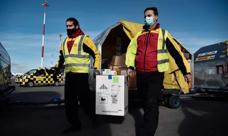 Workers carries boxes containing the Pfizer-BioNTech Covid-19 vaccine at an airport in Thessaloniki