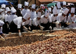 Oruro, Bolivia Cooks prepare a stew called charquekan, made with llama meat, potatoes, eggs and cheese, during the inauguration ceremony at the World Camelids Convention.