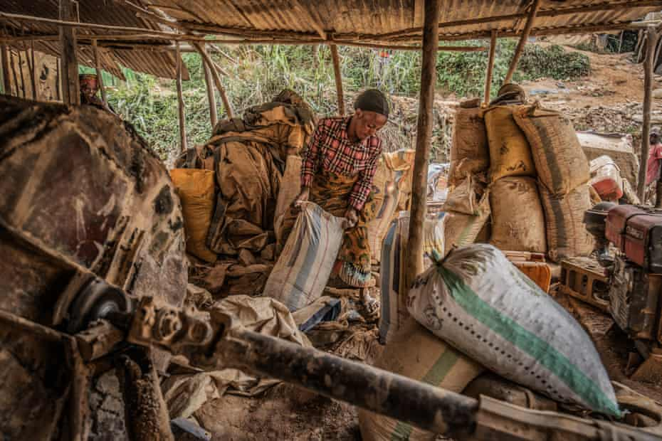 A woman loads sacks of sand to be filtered for gold particles at a mine in Kamituga.
