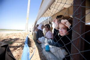 Young Syrians take shelter at a refugee camp on the Turkey-Syria border