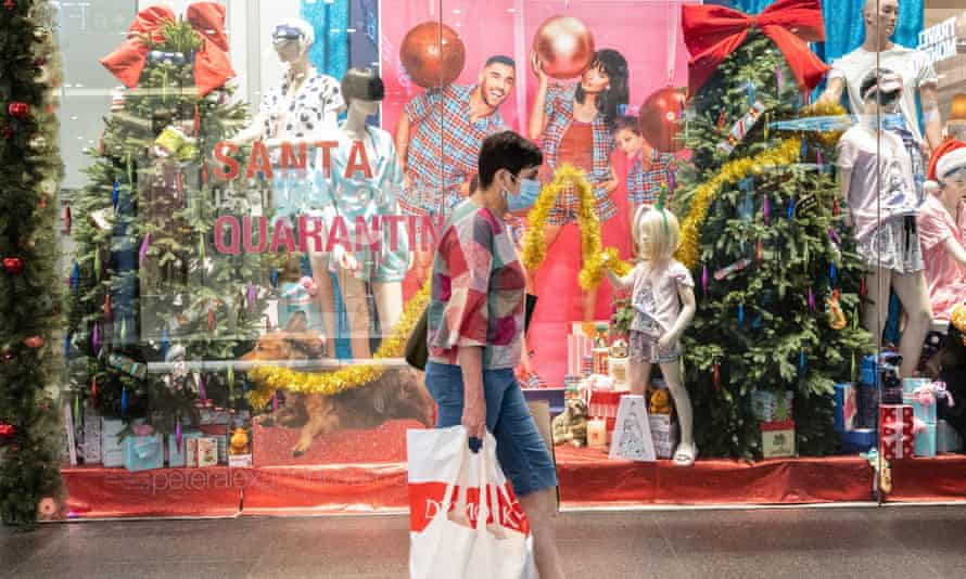 A woman wearing a face mask as she walks past a Christmas display
