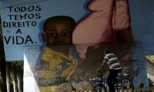 A man passes by graffiti of pregnancy on an overpass in Recife, Brazil.