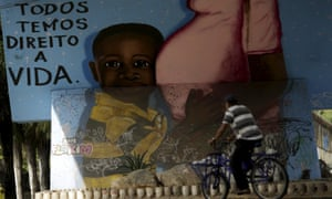 A man walks in front of a graffiti of pregnancy on an overpass in Recife, Brazil, 4 February 2016. The graffiti reads, 'We all have a right to live'.