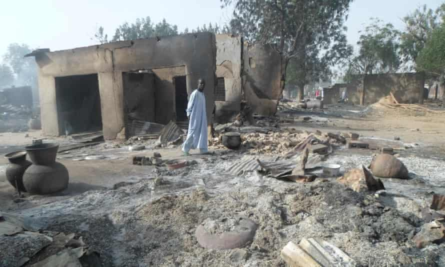 A man walks past burnt out houses following an attack by Boko Haram on Dalori village.