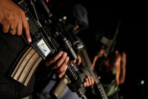 Young men presenting themselves as drug traffickers hold assault rifles decorated with Rio 2016 stickers in a favela the night before the Olympics closing ceremony