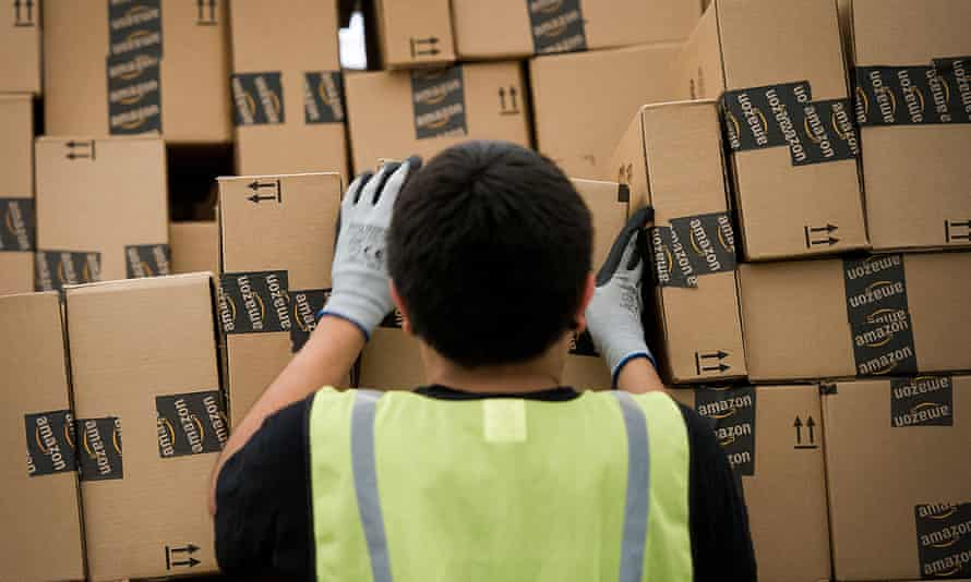 An employee loads a truck with boxes to be shipped at an Amazon distribution center in Phoenix, Arizona on 26 November 2012.
