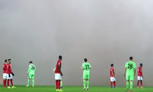 Players wait for smoke from the stands to clear.
