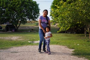 "María Rebecca, 23, and her three-year-old daughter in their backyard. Since was eight years of age she started helping her father picking up strawberries in Michoacán. At the age of 12 was when she began enjoying the work. María Rebecca would miss school to work in the fields so she could have money to buy snacks because her parents could not afford them. ""If you love your job, you are not going to care whether it is difficult or easy, you are just going to do it. I love my job."""