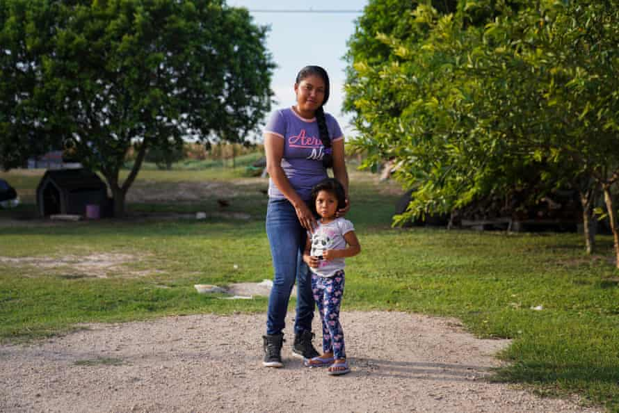 """María Rebecca, 23, and her three-year-old daughter in their backyard. Since was eight years of age she started helping her father picking up strawberries in Michoacán. At the age of 12 was when she began enjoying the work. María Rebecca would miss school to work in the fields so she could have money to buy snacks because her parents could not afford them. """"If you love your job, you are not going to care whether it is difficult or easy, you are just going to do it. I love my job."""""""