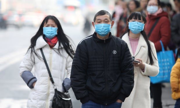 Chinese residents wear masks while waiting at a bus station near the closed Huanan seafood wholesale market, which has been linked to new strain of coronavirus.