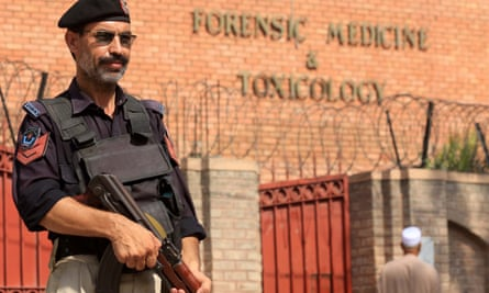 A Pakistani policeman stands guard outside a mortuary where the body of Tahir Ahmad Naseem was taken.