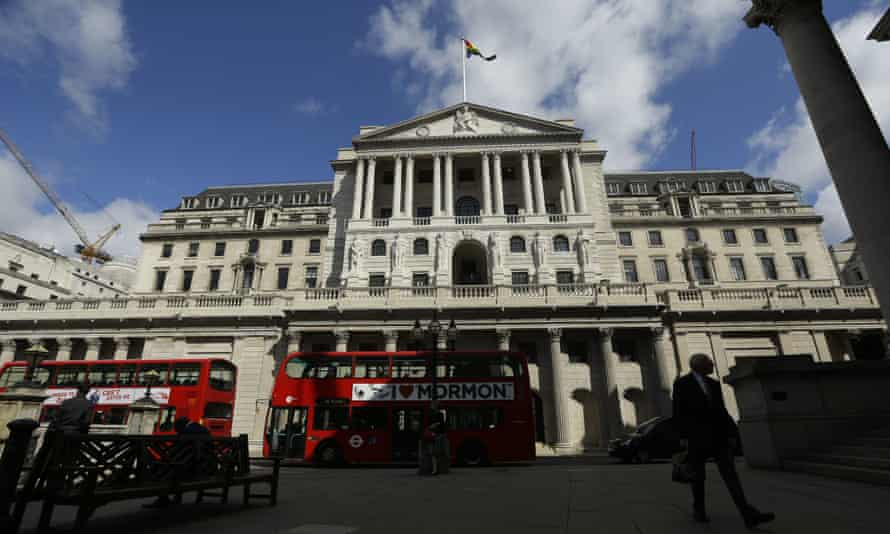 Buses pass the Bank of England, in the City of London.