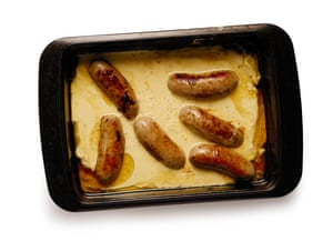 Batter mixture and sausages in baking tin