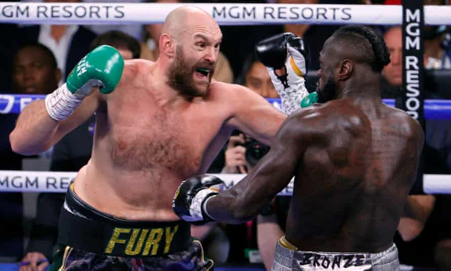 Tyson Fury (left) and Deontay Wilder trade blows in the first round.