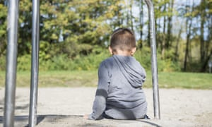 A boy sitting alone in a playground