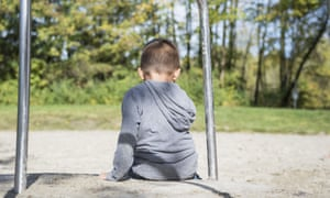 A young boy sits with his back to camera, alone on a playground roundabout