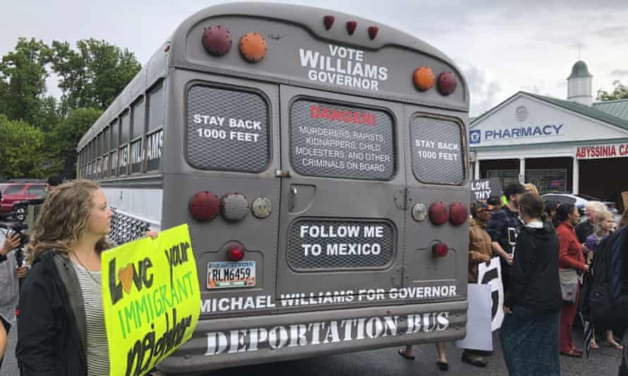 Protesters around the back of Michael Williams's 'deportation bus' in Clarkston, Georgia, on 16 May.]